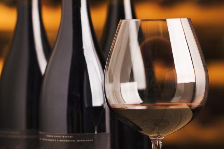 Weinflaschen und ein Glas Rotwein